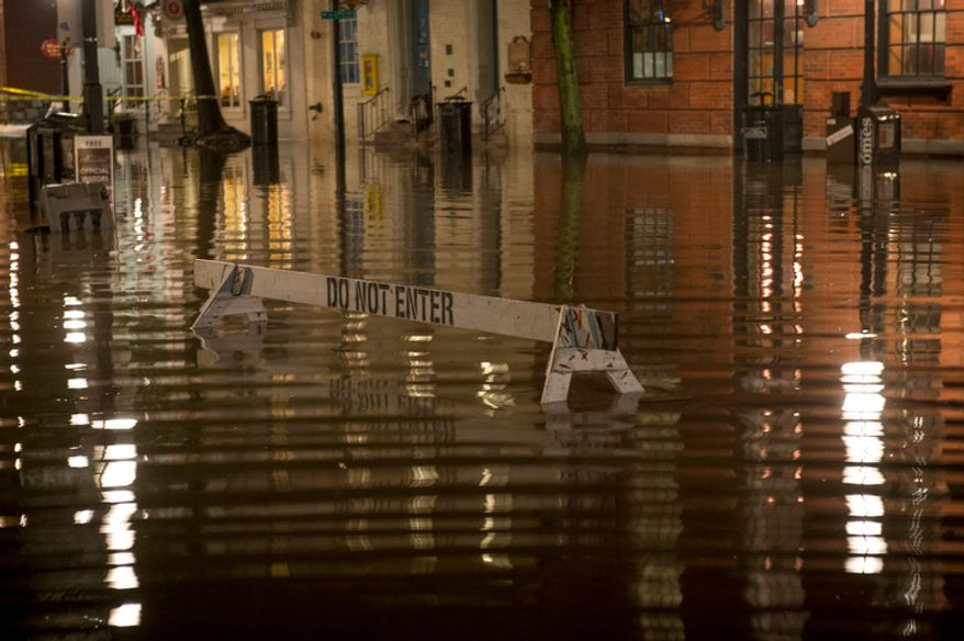 A barricade sits in the middle of the the intersection of King and S. Union Streets which is submerged in flood water from the Potomac River late into the night in Alexandria, Va., Tuesday, Oct. 30, 2012, the day after Hurricane Sandy slammed into the region. (Rod Lamkey Jr./The Washington Times)