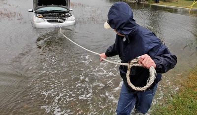 Glenn Heartley pulls on a rope attached to his car in preparation for getting it towed from a creek in Chincoteague, Va., Tuesday, Oct. 30, 2012. Heartley and his wife were swept off the road into the shallow creek during superstorm Sandy's arrival Monday. (AP Photo/Steve Helber)