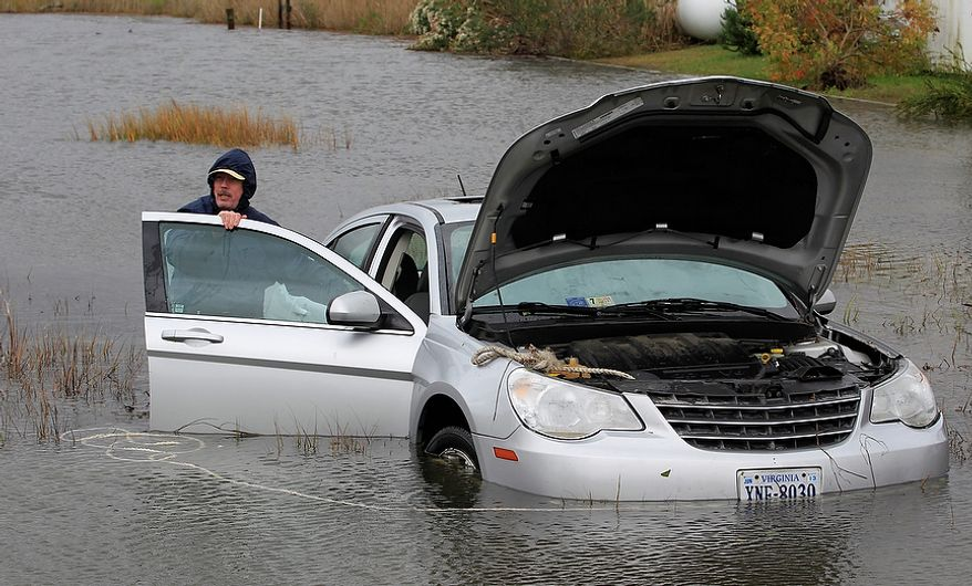 Glenn Heartley works on his car in a creek in Chincoteague, Va., Tuesday, Oct. 30, 2012. Heartley and his wife were swept off the road into a shallow creek when superstorm Sandy struck the area Monday. (AP Photo/Steve Helber)