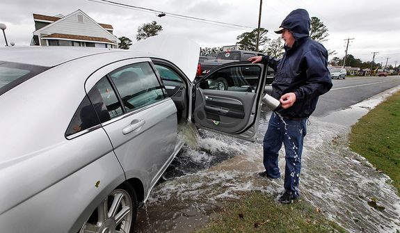 Glenn Heartley watches floodwaters from superstorm Sandy pour out of his car after it was pulled out of a creek in Chincoteague, Va., Tuesday, Oct. 30, 2012.  Heartley and his wife were swept off the road into a shallow creek during Monday's storm. (AP Photo/Steve Helber)