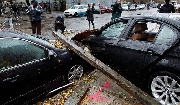 Onlookers take photographs of two cars that collided during flooding outside the Consolidated Edison power sub-station on 14th Street, Tuesday, Oct. 30, 2012, in New York. Hurricane Sandy marched slowly inland, leaving millions without power or mass transit, with huge swatches of the nation's largest city unusually vacant and dark. New York was among the hardest hit, with its financial heart in Lower Manhattan shuttered for a second day and seawater cascading into the still-gaping construction pit at the World Trade Center (AP Photo/ John Minchillo)
