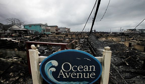 A sign for Ocean Avenue stands in the smoldering ruins of houses in the Breezy Point section of New York, Tuesday, Oct. 30, 2012. More than 50 homes were destroyed in a fire which swept through the oceanfront  community during superstorm Sandy. (AP Photo/Mark Lennihan)