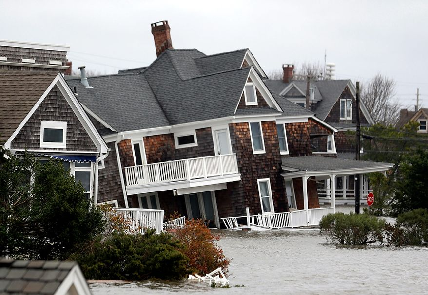 Floodwaters surround homes near the Mantoloking Bridge the morning after superstorm Sandy rolled through, Tuesday, Oct. 30, 2012, in Mantoloking, N.J. Sandy, the storm that made landfall Monday, caused multiple fatalities, halted mass transit and cut power to more than 6 million homes and businesses. (AP Photo/Julio Cortez)