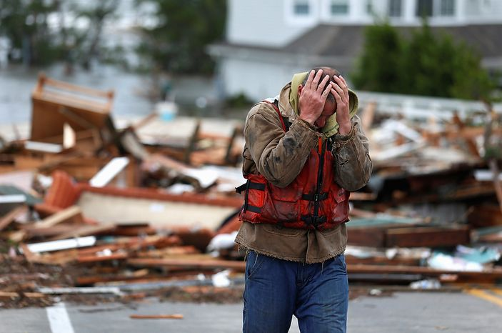 Brian Hajeski, 41, of Brick, N.J., reacts after looking at debris of a home that washed up on to the Mantoloking Bridge the morning after superstorm Sandy rolled through, Tuesday, Oct. 30, 2012, in Mantoloking, N.J. Sandy, the storm that made landfall Monday, caused multiple fatalities, halted mass transit and cut power to more than 6 million homes and businesses. (AP Photo/Julio