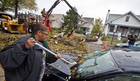 A resident on the 1100 block of Evarts St. NE removes debris left by a downed tree caused by hurricane Sandy, in Washington, D.C., Tuesday, October 30, 2012. The effects of hurricane Sandy have impacted many in the DC area.  (Andrew S. Geraci/The Washington Times)