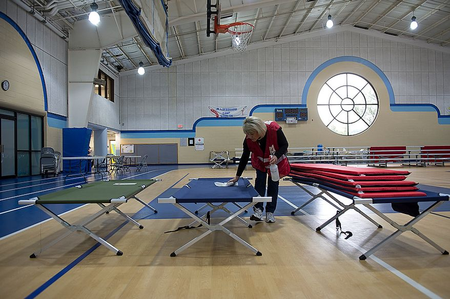 Red Cross volunteer Julie Tarascio wipes down one of the cots in the Lee District REC Center in Alexandria, Va., which served as an animal-friendly shelter for people needing to evacuate their homes due to Hurricane Sandy. They said they had about 23 people stay here Monday night, the youngest of which was 7 weeks old. This image was made Tuesday, Oct. 30, 2012. (Barbara L. Salisbury/The Washington Times)