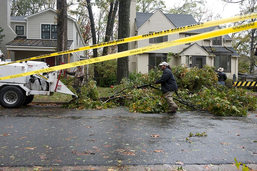 Workers with Zamudio's Complete Tree Service load branches from a downed tree into a shredder on Cameron Mills in the Beverly Hills neighborhood of Alexandria, Va., on Tuesday, Oct. 30, 2012. Hurricane Sandy brought down two large trees here, one of which fell across the street. The trees took down the power lines. Fortunately no one was hurt. (Barbara L. Salisbury/The Washington Times)