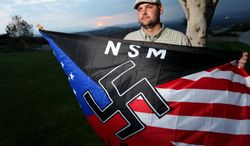 Jeff Hall holds a neo-Nazi flag while standing at Sycamore Highlands Park near his home in Riverside, Calif., in October 2010. (AP Photo/Sandy Huffaker) ** FILE **