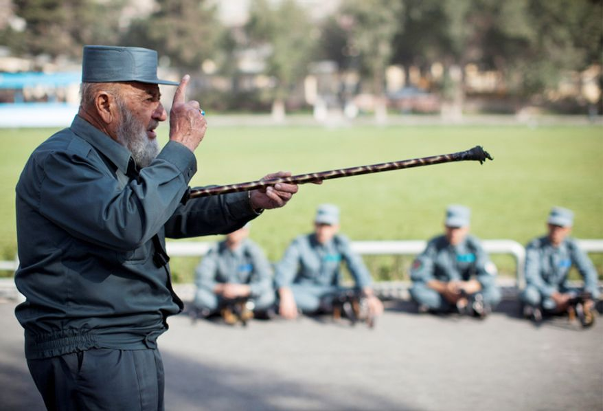 Afghan National Police instructor Ghulam Hazrat, left, 70, instructs recruits at the police academy in Kabul, Afghanistan. On Thursday, Oct. 18, 2012, President Hamid Karzai said that his military and police are prepared to take full responsibility for security if the American-led international coalition decides to speed up the handover. But international observers warn that the largely illiterate police force will disintegrate after 2014 into factional militias more loyal to local warlords than to the state. (AP Photo/Anja Niedringhaus)
