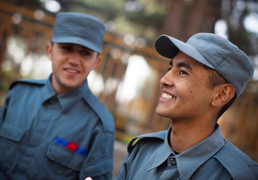 "Azim Aga, right, from northern Baghlan province, a fresh police recruit, smiles during a break at the police academy in Kabul, Afghanistan. ""Right now the police who are on the street are not educated and are from the jihad, a reference to Afghanistan's successive wars, 'We will be proud policemen.'"" Aga said. (AP Photo/Anja Niedringhaus)"