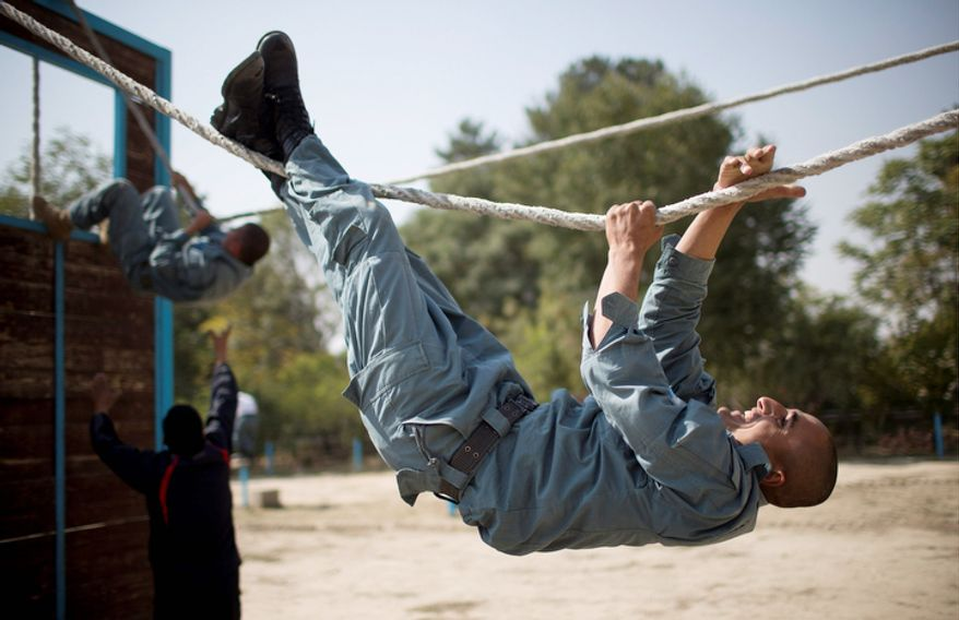 Afghan National Police officers navigate a ropes course during a training session at the police academy in Kabul, Afghanistan.  (AP Photo/Anja Niedringhaus)