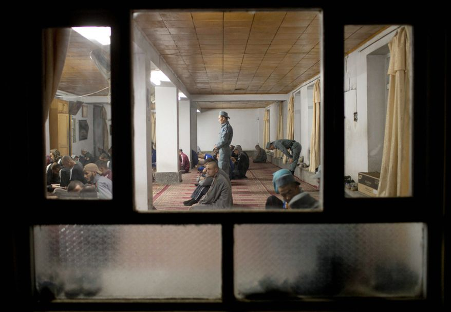 Police officers participate in early morning prayers inside a mosque at the police academy in Kabul, Afghanistan.  (AP Photo/Anja Niedringhaus)