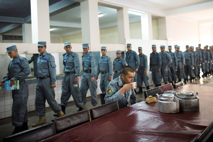 Afghan National Police officers line up for breakfast after prayers at the police academy in Kabul, Afghanistan.  (AP Photo/Anja Niedringhaus)