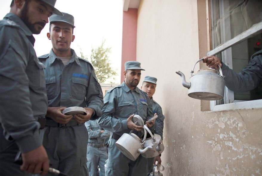 Police officers line up to take their tea pots for breakfast at the police academy in Kabul, Afghanistan. The readiness of Afghanistanís security forces is central to U.S. and NATO plans to withdraw all forces from the country by the end of 2014, and the academyís new commander wants to help turn around a 146,000-strong national police force long riddled with corruption, incompetence and factional rivalries. (AP Photo/Anja Niedringhaus)