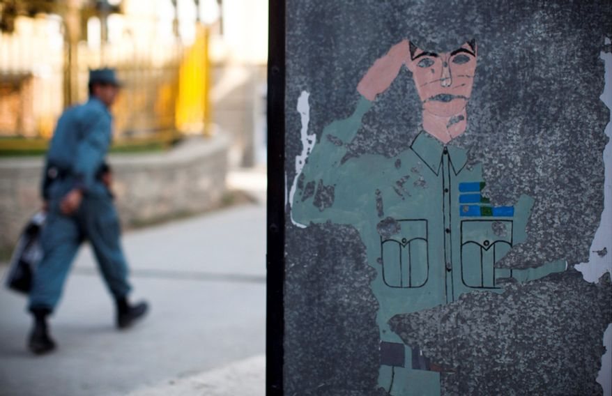 In this Tuesday, Oct. 9, 2012 photo, a police instructor passes by a wall painting at the police academy in Kabul, Afghanistan. (AP Photo/Anja Niedringhaus)