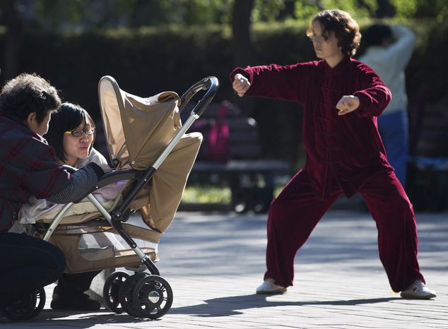 A Chinese woman performs a morning exercise next to a family members having a light moment with their infant at the Ritan Park in Beijing Wednesday, Oct. 31, 2012. A government think tank says China should start phasing out its one-child policy im