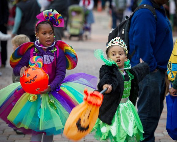 Skye Gill (left), 6, and her cousin Taylor Kearney (right), 6, both of Washington, play while waiting in line for balloons as they and others arrive for Halloween festivities at Eastern Market in Washington on Wednesday,