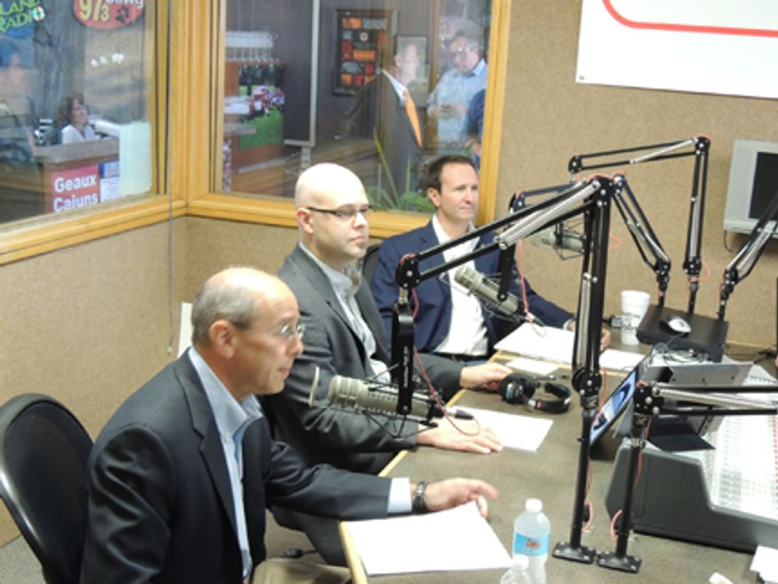 **FILE** U.S. Reps. Charles Boustany Jr., foreground, and Jeff Landry, back, prepare to debate in a radio studio in Lafayette, La.. Between the Republicans is Jeremy Lawrence, the moderator, of KPEL-FM. (Robert Buckman/Special to The Washington Times)