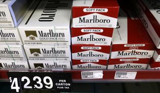 **FILE** Cartons of cigarettes sit on shelves at Discount Smoke Shop on Oct. 31, 2012, in Ballwin, Mo. (Associated Press)