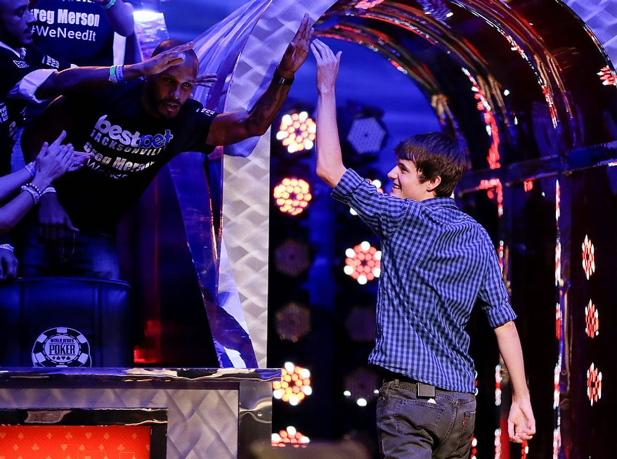 Arizona State senior Jake Balsiger, right, high fives members of the audience as he exits the floor after being eliminated from play during the World Series of Poker Final Table event, Wednesday, Oct. 31, 2012, in Las Vegas. (AP Photo/Julie Jacobson)