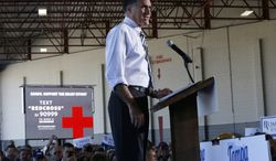 A sign telling supporters how to donate to the Red Cross for superstorm Sandy victims is seen at left as Republican presidential candidate Mitt Romney campaigns in Tampa, Fla., on Wednesday, Oct. 31, 2012. (AP Photo/Charles Dharapak)