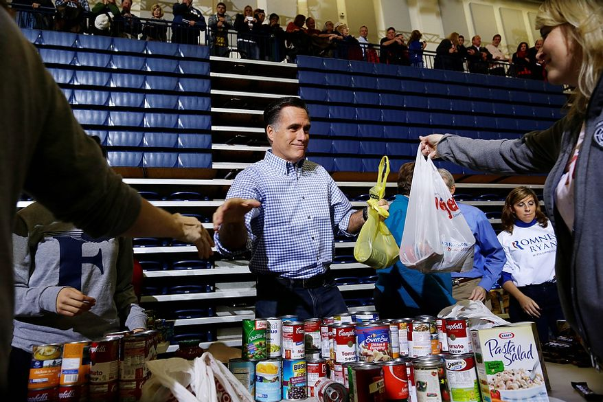 Republican presidential candidate, former Massachusetts Gov. Mitt Romney receives bags of food as he participates in a campaign event collecting supplies from residents local relief organizations for victims of superstorm Sandy, Tuesday, Oct. 30, 2012, at the James S. Trent Arena in Kettering, Ohio. (AP Photo/Charles Dharapak)
