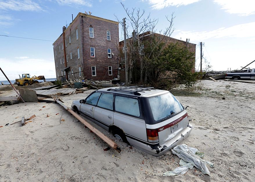 A car is partially buried by sand that was washed ashore by superstorm Sandy in Atlantic City, N.J., Wednesday, Oct. 31, 2012. (AP Photo/Patrick Semansky)