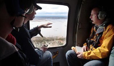 Collin O'Mara briefs Gov. Jack Markell, right, and Lt. Gov. Matt Denn as they tour Delaware's shores by National Guard Blackhawk helicopter in the wake of Sandy, Tuesday afternoon, Oct. 30, 2012, in Bethany Beach, Del. (AP Photo/The Wilmington News-Journal, William Bretzger)