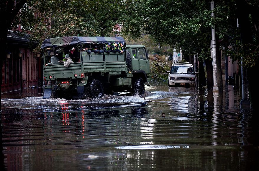 Members of the National Guard and Hoboken Police ride a large truck through floodwaters used to pluck people from high water in Hoboken, N.J., Wednesday, Oct. 31, 2012, in the wake of superstorm Sandy. Parts of the city are still covered in standing water, trapping some residents in their homes. (AP Photo/Craig Ruttle)