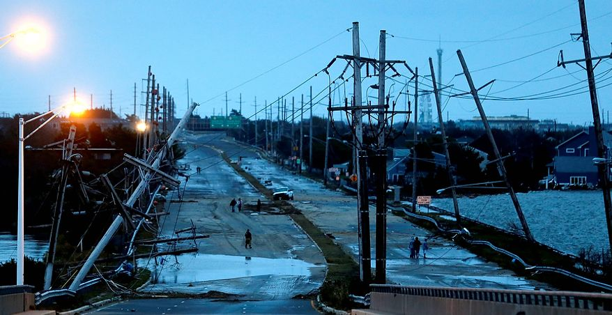 Downed power lines and a battered road is what superstorm Sandy left behind as people walk off the flooded Seaside Heights island, Tuesday, Oct. 30, 2012. Sandy, the storm that made landfall Monday, caused multiple fatalities, halted mass transit and cut power to more than 6 million homes and businesses. (AP Photo/Julio Cortez)