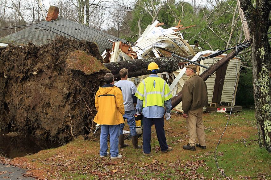 A cleanup crew works to figure out how to remove power lines and trees off a summer cottage on Lake Webster, Wednesday, Oct. 31, 2012 in Franklin, N.H. By midday Wednesday, utilities brought the number of New Hampshire homes and businesses without power down to 70,000 from a peak of 210,000. (AP Photo/Jim Cole)