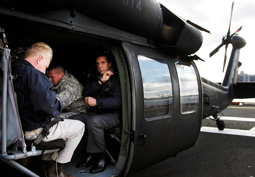 Gov. Andrew Cuomo, right, adjusts his shoulder straps as he prepares to take a flight in a New York Air National Guard helicopter Wednesday, Oct. 31, 2012 in New York. The governor was joined by Sen. Kirsten Gillibrand, D-NY, Sen. Charles Schumer, D-NY, and local officials for the flight over the city, Nassau and Westchester counties to get an assessment of damages from superstorm Sandy. (AP Photo/Mark Lennihan)
