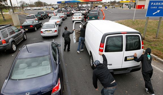 People help push John Oh's van to the pumps at the New Jersey Turnpike's Thomas A. Edison service area Wednesday, Oct. 31, 2012, near Woodbridge, N.J., after Oh, of Blue Bell, Pa., ran out of gas waiting in a long line near exit 11. After Monday's storm surge from Sandy, many gas stations in the region are without power and those that are open have very long lines. (AP Photo/Mel Evans)