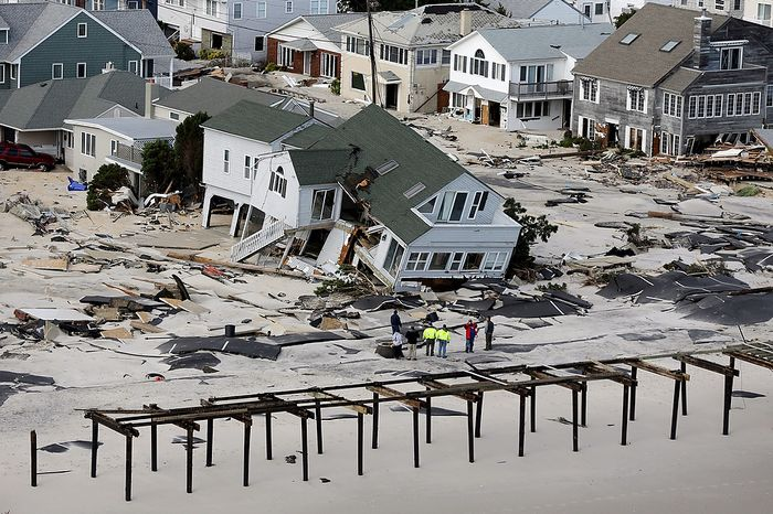 People survey the destruction left in the wake of Superstorm Sandy on Wednesday, Oct. 31, 2012, in Seaside Heights, N.