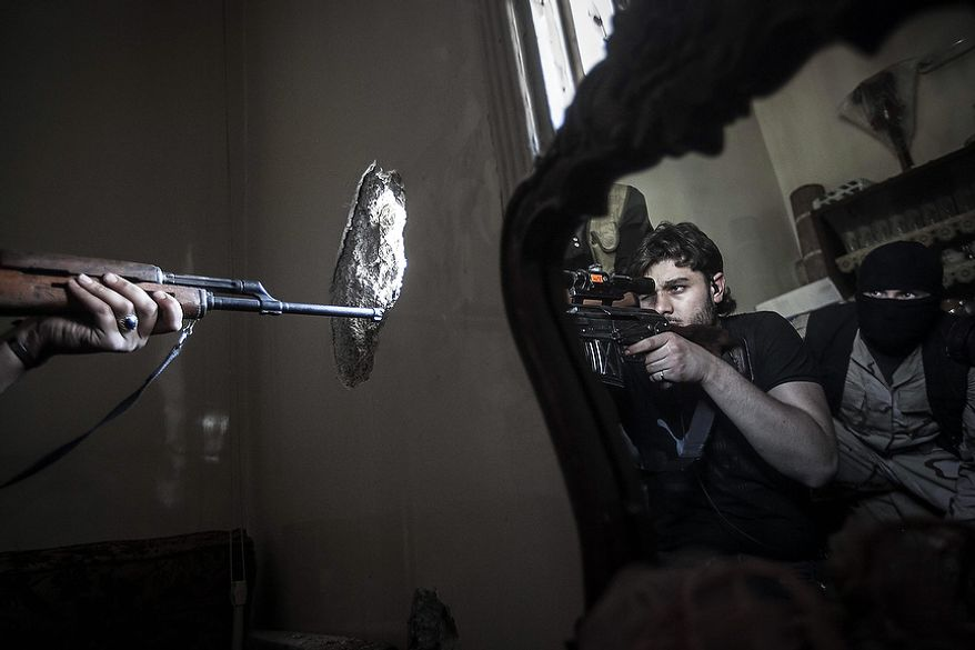 In this Monday, Oct. 29, 2012, photo, a rebel sniper aims at a Syrian army position, seen with another rebel fighter reflected in a mirror, in a residential building in the Jedida district of Aleppo, Syria. Syrian fighter jets pounded rebel areas across the country on Monday with scores of airstrikes that anti-regime activists called the most widespread bombing in a single day since Syria's troubles started 19 months ago. (AP Photo/Narciso Contreras)