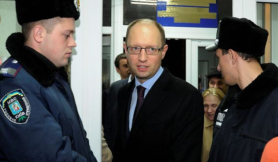 Ukrainian opposition leader Arseniy Yatsenyuk (center) arrives at a district election commission in Kiev on Tuesday, Oct. 30, 2012. Ukrainian opposition parties on Tuesday appeared split over whether to recognize the ruling party's victory in a parliamentary election denounced as unfair by international observers. (AP Photo/Sergei Chuzavkov)
