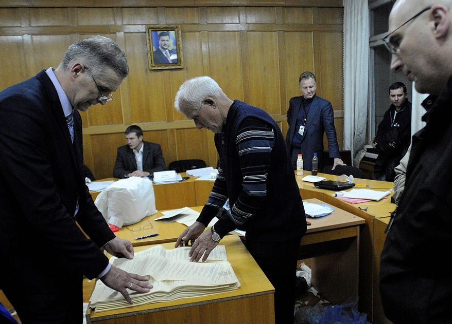 Election commission officials recalculate ballots at a district election commission in Kiev on Tuesday, Oct. 30, 2012. Ukrainian opposition parties on Tuesday appeared split over whether to recognize the ruling party's victory in a parliamentary election denounced as unfair by international observers. (AP Photo/Sergei Chuzavkov)