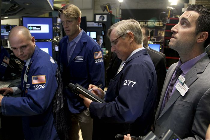 Traders work on the floor at the New York Stock Exchange on Wednesday, Oct. 31, 2012, in New York. Traffic is snarled, subways out of commission, streets flooded and power out in many parts of the city, but the exchange opened without hitch Wednesday after a historic two-day shutdown, courtesy of Hurricane Sandy. (AP Photo/Seth Wenig)