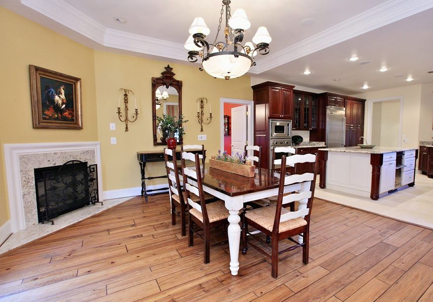Adjacent to the kitchen is a breakfast area with a fireplace.