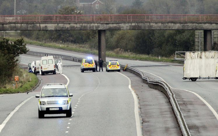 Police and forensic officers examine the scene of a fatal shooting of a Northern Ireland prison officer on the M1 motorway near Lurgan, Northern Ireland, on Thursday. He was killed in an ambush as he was driving to work. (Associated Press)