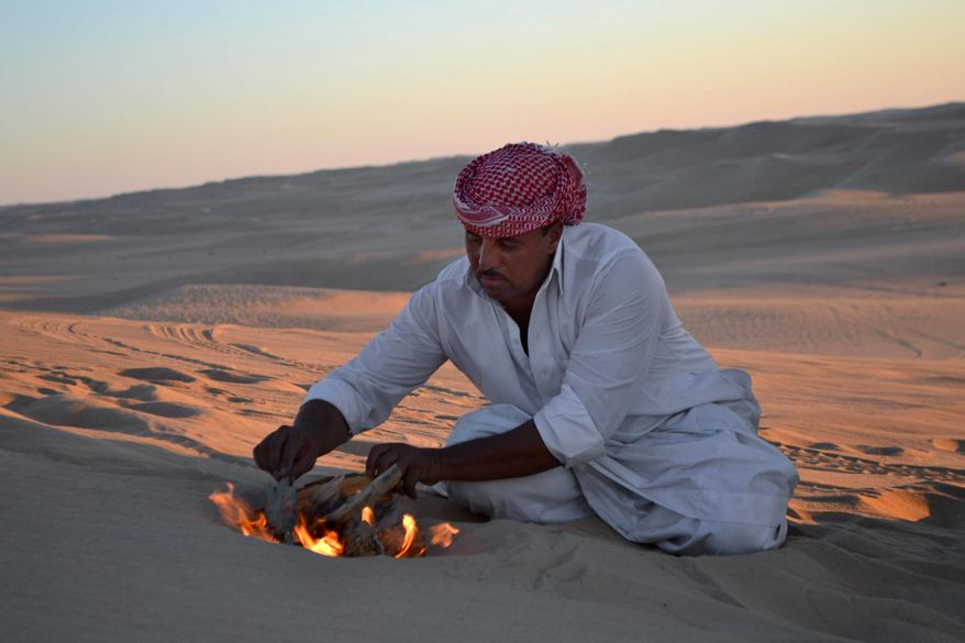 This September 2012 photo shows desert safari driver Ahmed Bakrin building a small bonfire to make mint tea before sunset during a trek through the Great Sand Sea outside the Egyptian oasis of Siwa, a Berber town of some 27,000 people roughly 450 miles (about 725 kilometers) southwest of Cairo. The palm tree-lined area is known for its quiet charm, ancient ruins, abundant natural springs, a vast salt lake and rolling sand dunes in the surrounding desert. (AP Photo/Kim Gamel)