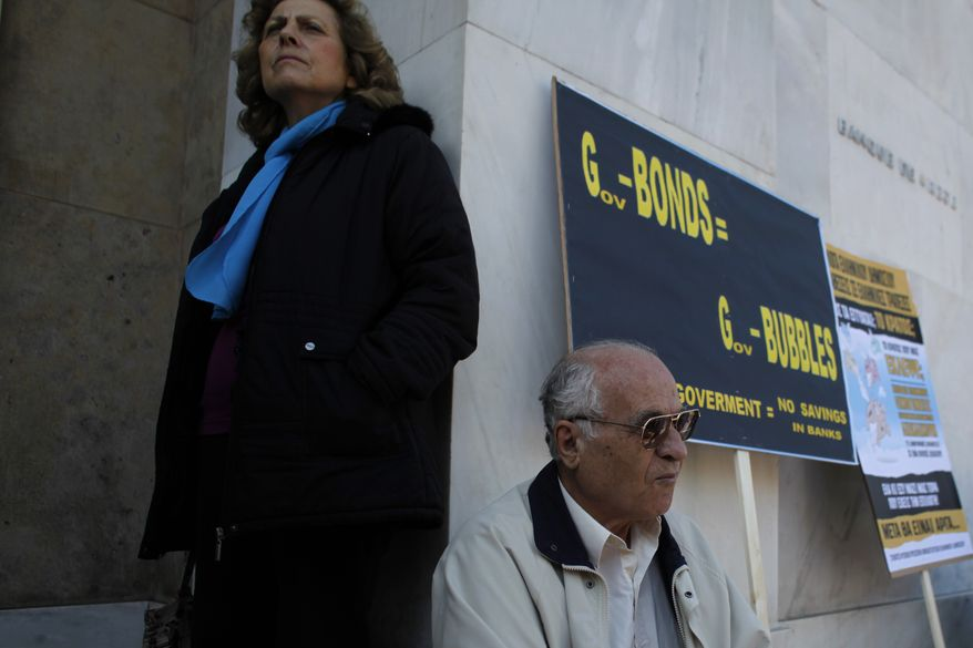 Greek bondholders stand at the entrance to Greece's central bank during a protest in Athens on Wednesday, Oct. 31, 2012. (AP Photo/Kostas Tsironis)