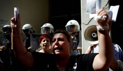 In this Sept. 28, 2012 file photo, private hospital nurse Paraskevi Petropoulou holds up her unpaid electricity and income tax bills during a protest outside the Health Ministry in central Athens. Petropoulou said that she has not been paid for more than five months, because the government owes money to private hospitals who in turn are unable to pay their employees. To the casual visitor, all might appear well in Athens, but scratch the surface and you find a society in freefall, ripped apart by the most vicious financial crisis the country has seen in half a century. (AP Photo/Petros Giannakouris, File)