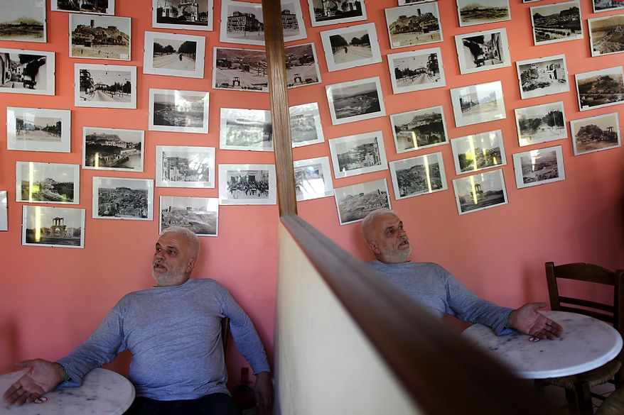 In this Tuesday Sept. 25, 2012 file photo a coffee shop owner tells journalists that he has had an 80 percent drop in his business, in Athens. To the casual visitor, all might appear well in Athens. But scratch the surface and you find a society in freefall, ripped apart by the most vicious financial crisis the country has seen in half a century.(AP Photo/Petros Giannakouris)