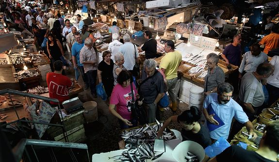 In this Monday, Sept. 24, people walk inside the Athens' central fish market. To the casual visitor, all might appear well in Athens. But scratch the surface and you find a society in freefall, ripped apart by the most vicious financial crisis the country has seen in half a century. (AP Photo/Petros Giannakouris)