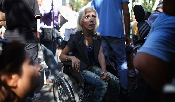 In this Sept. 27, 2012, file photo, Anastasia Mouzakiti, center, a paraplegic, came to the demonstration from the northern city of Thessaloniki with her husband, to protest outside the Greek parliament. To the casual visitor, all might appear well in Athens, but scratch the surface and you find a society in freefall, ripped apart by the most vicious financial crisis the country has seen in half a century. (AP Photo/Petros Giannakouris)