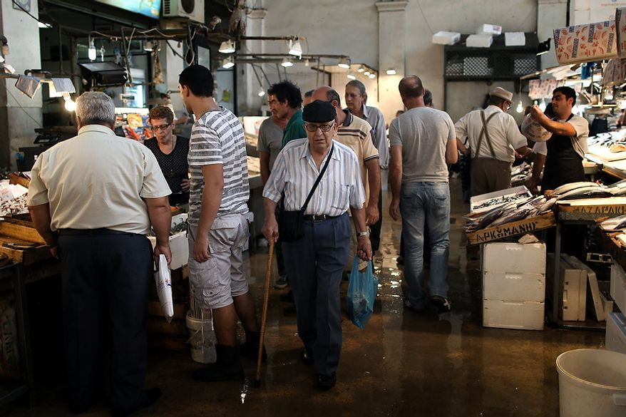 In this Monday, Sept. 24, file photo an elderly man walks inside the Athens' central fish market. To the casual visitor, all might appear well in Athens. But scratch the surface and you find a society in freefall, ripped apart by the most vicious financial crisis the country has seen in half a century. (AP Photo/Petros Giannakouris)