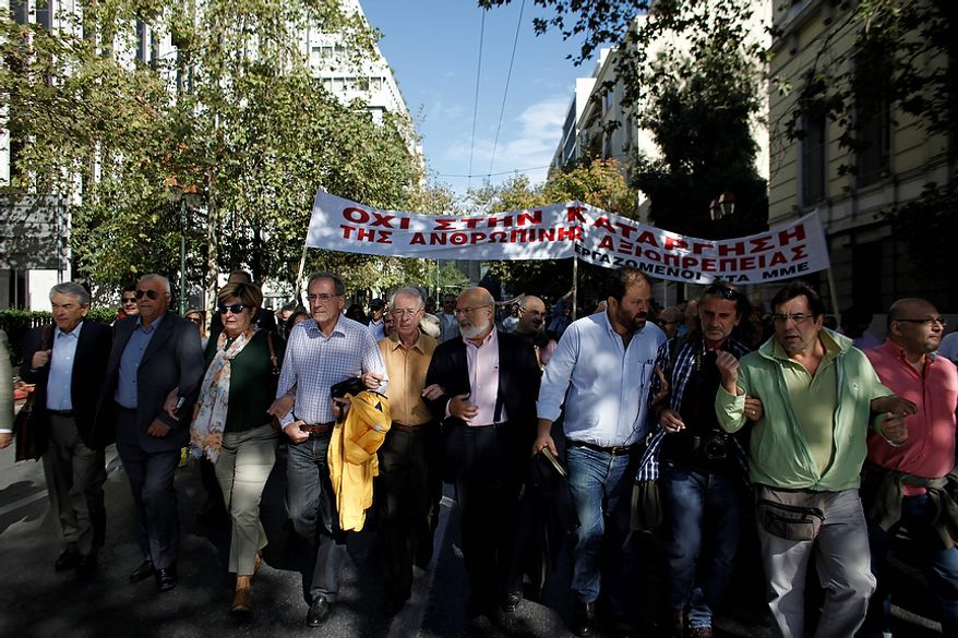 "Journalists march in central Athens during a protest, Wednesday, Oct. 31 2012. The banner reads ""Don't Ax Human Dignity"". Greece's two main labor unions covering civil servants and the private sector have called a 48-hour strike to protest austerity measures due to be voted on next week. The strike call came as the finance minister submitted an amended 2013 budget that raised the country's debt and deficit forecasts for next year. (AP Photo/Kostas Tsironis)"