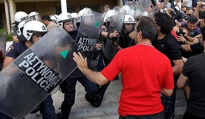 In this Oct. 4, 2012, file photo, riot police clash with protesters inside Greece's Defense Ministry in Athens. Police clashed with scores of protesting shipyard workers after they forced their way into the grounds of Greece's Defense Ministry. The workers say they have not been paid in months. To the casual visitor, all might appear well in Athens, but scratch the surface and you find a society in freefall, ripped apart by the most vicious financial crisis the country has seen in half a century. (AP Photo/Thanassis Stavrakis, File)