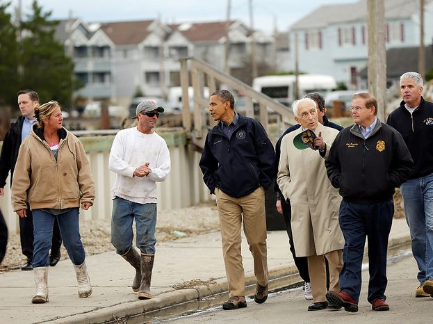 President Obama (center) talks with a resident as he tours a neighborhood affected by superstorm Sandy, on Wednesday, Oct. 31, 2012, in Brigantine, N.J. Walking with Mr. Obama are Sen. Frank Lautenberg and Sen. Bob Menende